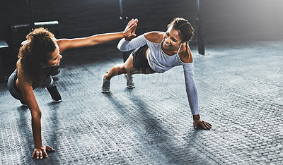 Buy stock photo Shot of two young women giving each other a high five while doing push ups at the gym