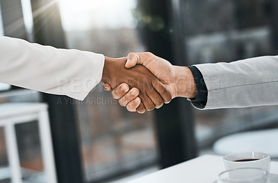 Buy stock photo Cropped shot of a businessman and businesswoman shaking hands in a modern office