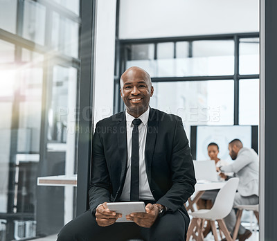Buy stock photo Shot of a mature businessman using a digital tablet in a boardroom with his colleagues in the background