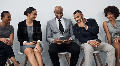 Buy stock photo Shot of a businessman using his digital tablet while waiting in line against a grey background