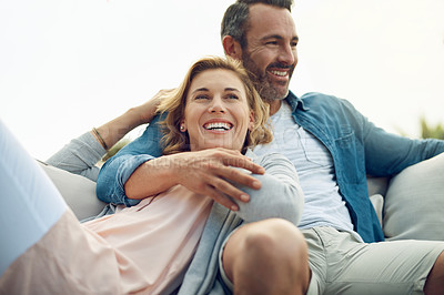 Buy stock photo Cropped shot of an affectionate mature couple relaxing on a sofa outdoors
