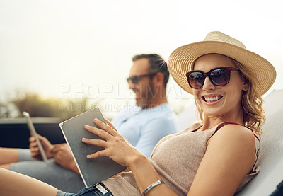 Buy stock photo Cropped portrait of an attractive mature woman reading a book while relaxing outdoors with her husband