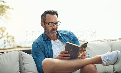 Buy stock photo Cropped shot of a handsome mature man reading a book while sitting outside