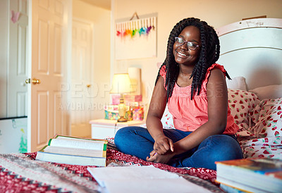Buy stock photo Shot of an adorable little girl doing her homework on her bed in her bedroom