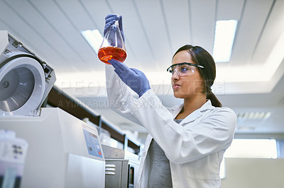 Buy stock photo Shot of a young scientist examining liquid in a beaker in a laboratory