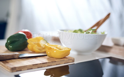 Buy stock photo Still life shot of peppers on a chopping board in a kitchen