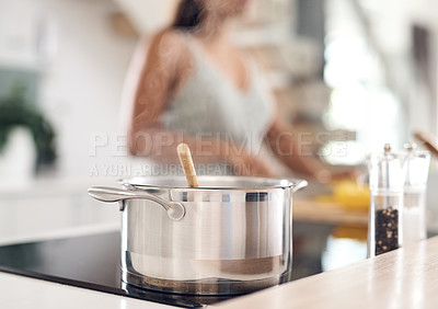 Buy stock photo Closeup shot of a pot on the stove with a woman in the background