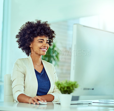 Buy stock photo Shot of a young businesswoman using a computer at her desk in a modern office