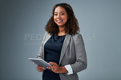 Buy stock photo Studio portrait of a young businesswoman using a digital tablet against a grey background