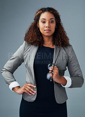 Buy stock photo Studio portrait of a young businesswoman posing against a grey background