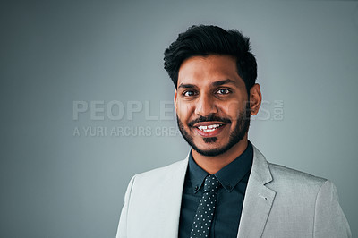 Buy stock photo Studio portrait of a young businessman posing against a grey background