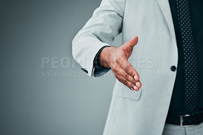 Buy stock photo Closeup shot of an unrecognizable businessman extending a handshake against a grey background