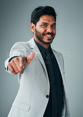Buy stock photo Studio portrait of a young businessman pointing his finger at the camera against a grey background