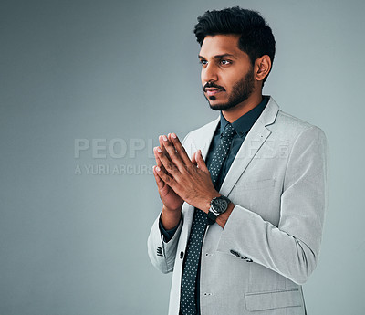 Buy stock photo Studio shot of a young businessman posing with his hands together against a grey background