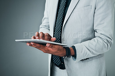 Buy stock photo Closeup shot of an unrecognizable businessman using a digital tablet against a grey background