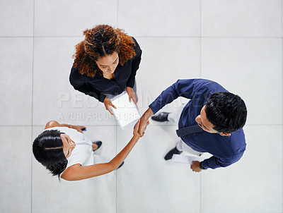 Buy stock photo High angle shot of two young businesspeople shaking hands while standing in their office lobby