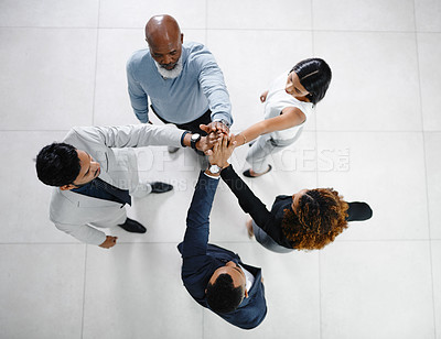 Buy stock photo High angle shot of a group of businesspeople standing with their hands in a huddle in the office lobby