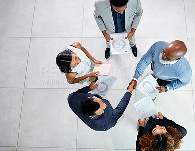 Buy stock photo High angle shot of two businessmen shaking hands while standing in their office lobby