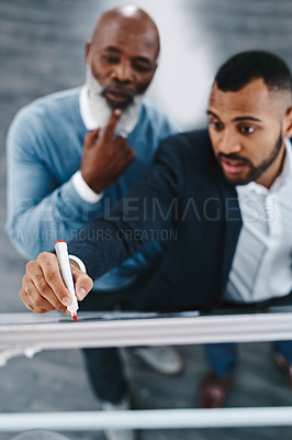 Buy stock photo High angle shot of two businessmen brainstorming together on a whiteboard in an office