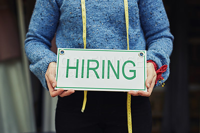 Buy stock photo Cropped shot of a designer holding up a hiring sign