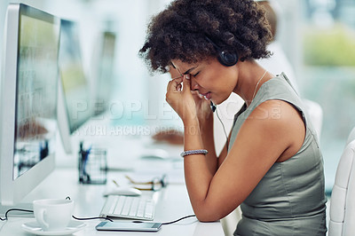 Buy stock photo Shot of a call centre agent looking stressed out while working in an office