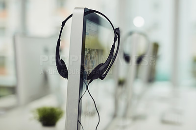 Buy stock photo Closeup shot of a headset hanging on a computer screen in an office