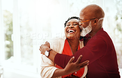 Buy stock photo Shot of a mature man affectionately kissing his wife at home