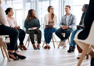 Buy stock photo Shot of a group of businesspeople sitting in a circle and having a meeting in a modern office