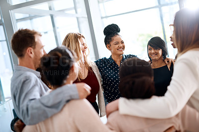 Buy stock photo Shot of a group of young businesspeople huddled together in solidarity in a modern office