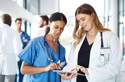 Buy stock photo Cropped shot of a female doctor and a female nurse using a tablet in the hospital with their colleagues in the background