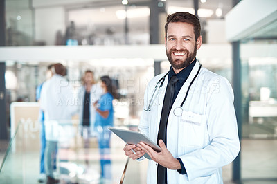 Buy stock photo Cropped portrait of a handsome male doctor using his tablet while standing in the hospital