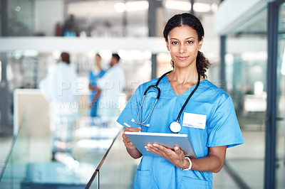 Buy stock photo Cropped portrait of an attractive young female nurse using her tablet while standing in the hospital
