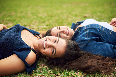 Buy stock photo Cropped shot of two female best friends lying on the grass in a public park
