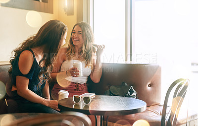 Buy stock photo Cropped shot of two attractive young women chilling in their local cafe