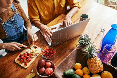 Buy stock photo Cropped shot of a young man using his laptop while his girlfriend is busy cutting fruit