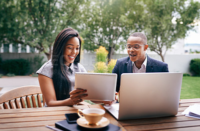 Buy stock photo Shot of a young businesswoman and businessman using a digital tablet while having a discussion outdoors
