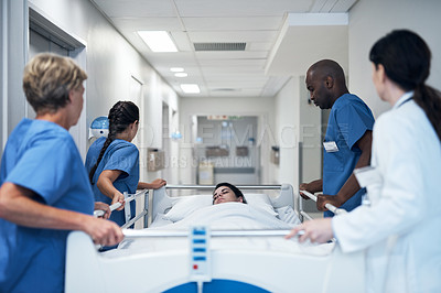 Buy stock photo Rearview shot of a medical team pushing a patient down the hallway in a gurney