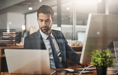 Buy stock photo Shot of a young businessman working late in an ofice
