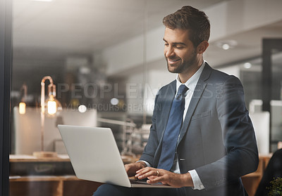 Buy stock photo Shot of a young businessman working late on a laptop in an office