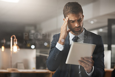 Buy stock photo Shot of a young businessman looking stressed out while working on a digital tablet at night in an office