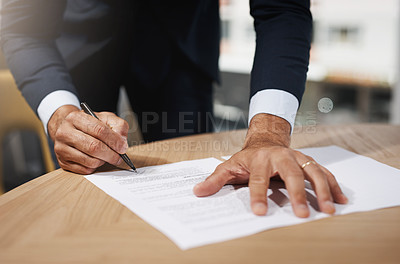 Buy stock photo Closeup shot of an unrecognizable businessman going through paperwork in an office