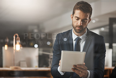 Buy stock photo Shot of a young businessman using a digital tablet while working late in an office