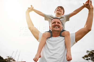 Buy stock photo Low angle shot of a mature man carrying his young son on his shoulders outside