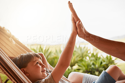 Buy stock photo Cropped shot of an unrecognizable man and his young son high fiving while lying outside on a hammock