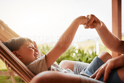 Buy stock photo Cropped shot of an unrecognizable man and his young son fist bumping while lying outside on a hammock