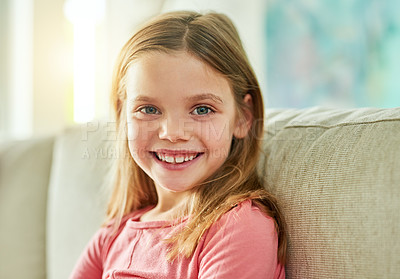 Buy stock photo Cropped portrait of an adorable little girl sitting on a sofa at home