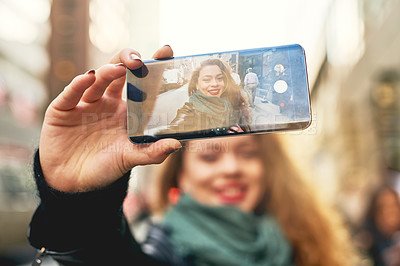Buy stock photo Cropped shot of a young woman taking selfies while out in the city