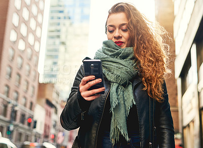 Buy stock photo Shot of a young woman using her cellphone while out in the city