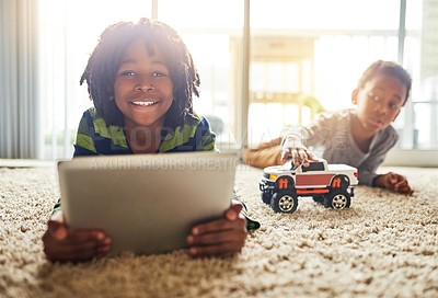 Buy stock photo Shot of a little boy using his digital tablet while his brother plays in the background