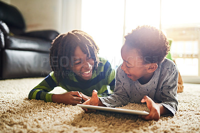 Buy stock photo Shot of two little boys using a digital tablet together